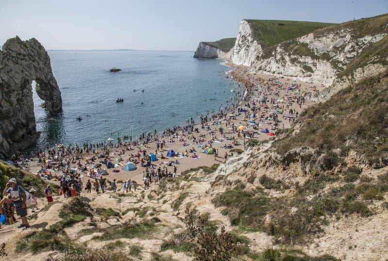 People sunbathing and having fun - Durdle Door, Dorset, England. stock photo