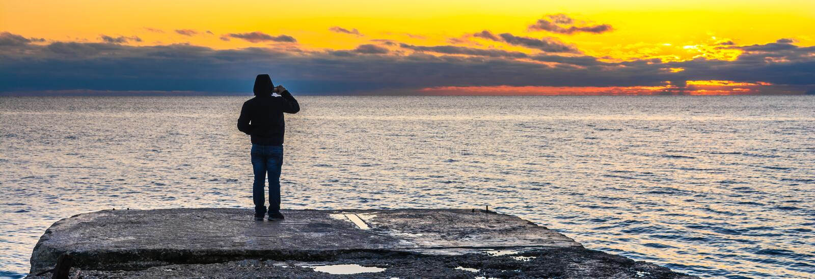 People at sunset. Man at sunset by the sea royalty free stock photos