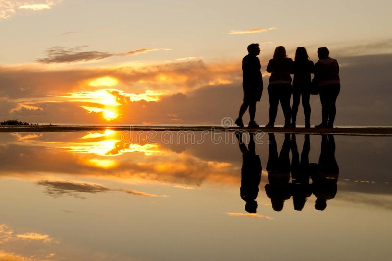 People at sunset. With reflection in water stock photography