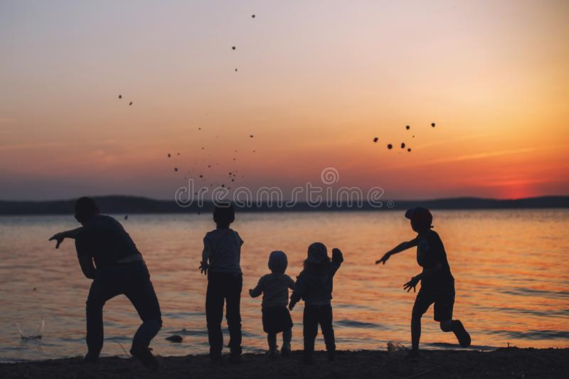 People  throwing stones into the water. dad with children. People at sunset throwing stones into the water. dad with children stock photos