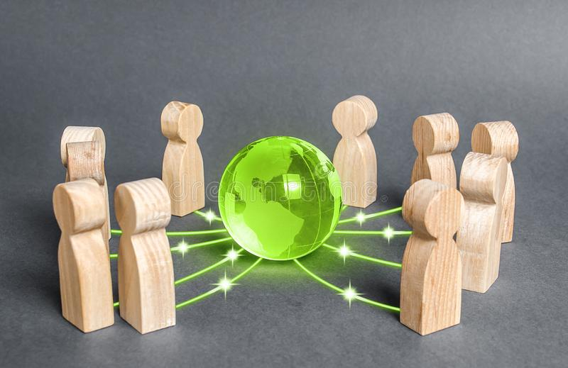 People surrounded a green globe planet earth. Cooperation and collaboration of people around the world. Outsourcing and joint work on projects. Diplomacy royalty free stock image