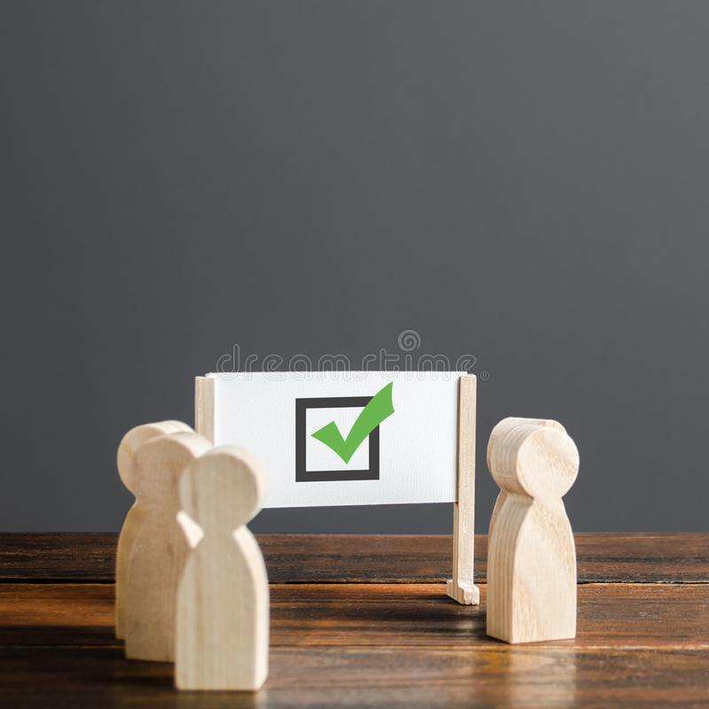 People surrounded a whiteboard with a green checkmark. Right collective choice, smart strategy and foresight. Voting. In an election. Verification of royalty free stock photo
