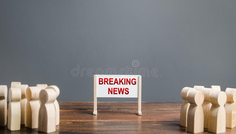 People surrounded a whiteboard with the words breaking news. Important events and incidents, extraordinary situations. Attract. Public attention. Message and stock photography