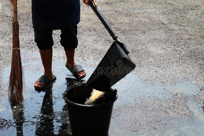 People are sweeping dirty water at ground streets, cleaner floor, housemaid, housekeeper, homemaker, maidservant, maid. The people are sweeping dirty water at stock image