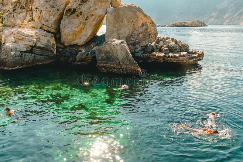 People swim with masks in the clear turquoise water of the Gulf of Oman stock photo