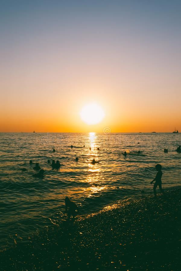 People swim in the sea at sunset royalty free stock image