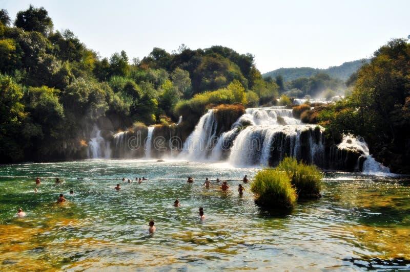 People Swimming Near Waterfall during Daytime stock photo