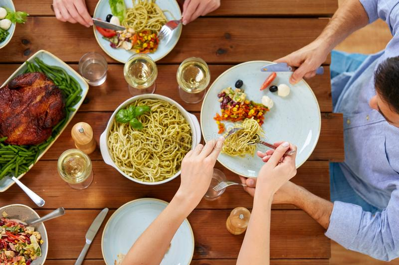 People at table with food eating pasta for dinner. Food, thanksgiving day, eating and leisure concept - people with pasta having dinner royalty free stock photography