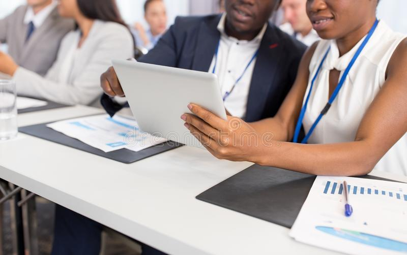 People with tablet computer at business conference stock images