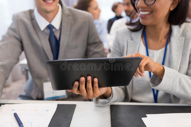 People with tablet computer at business conference royalty free stock image