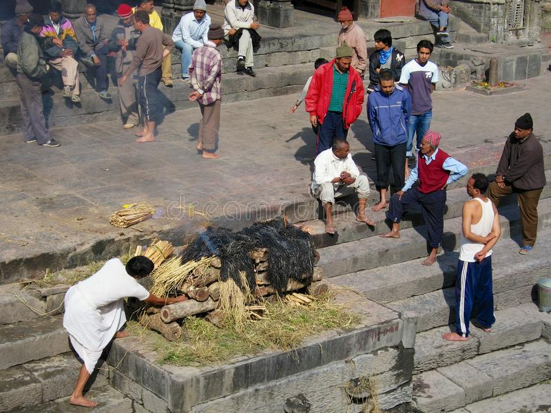 People take part in traditional cremation ceremony at the Pashupatinath temple on the Bagmati River bank in Kathmandu, Nepal. royalty free stock photo