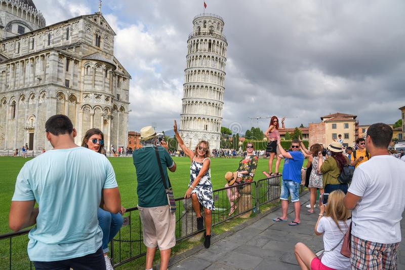 People take pictures in funny poses in front Leaning Tower in Pisa, Italy stock image