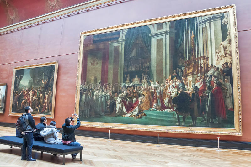 People taking photo of the Coronation of Napoleon (Louvre Museum). Paris, France - January 11, 2015: The Coronation of Napoleon (1807) at the Louvre Museum stock image