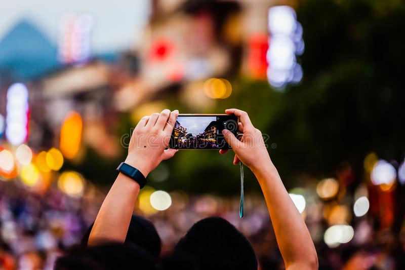 People Taking photos of crowds with mobile phone stock photos