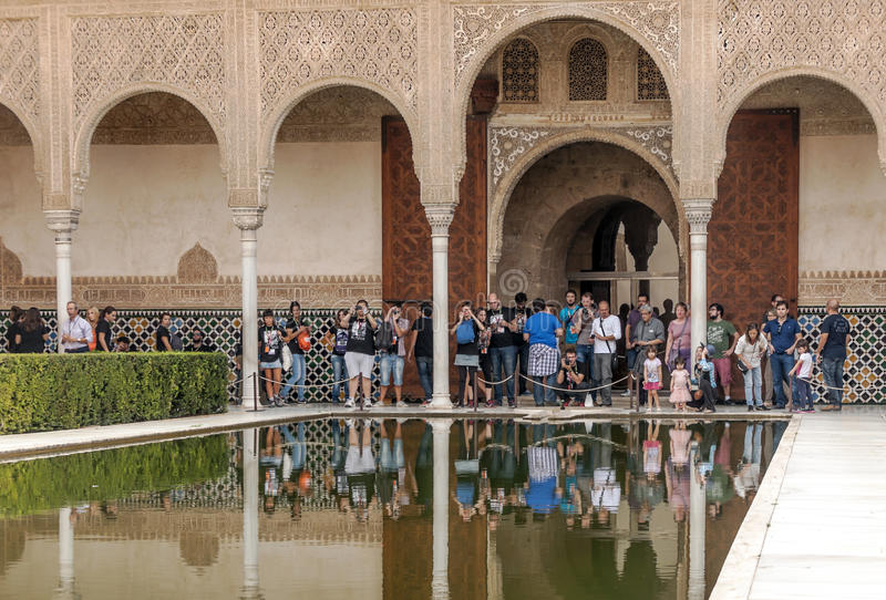 People taking photos in Alhambra. People taking photos in the pond of the Alhambra in Granada, Spain on a sunny day. It is an editorial image taken in October stock images