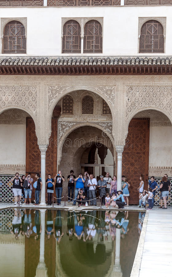 People taking photos in Alhambra. People taking photos in the pond of the Alhambra in Granada, Spain. It is a vertical image on a sunny day. It is an editorial royalty free stock photo