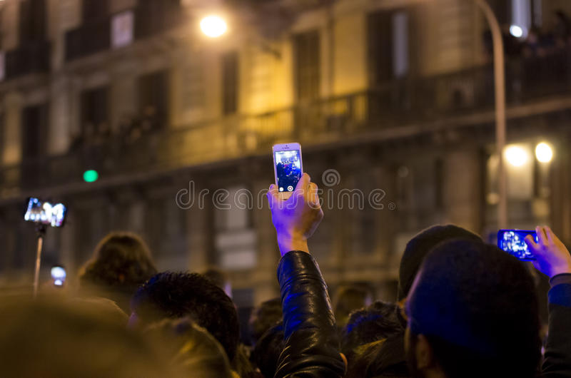 People taking photos. People on a crowded street taking pictures with their mobile phones during a celebration event