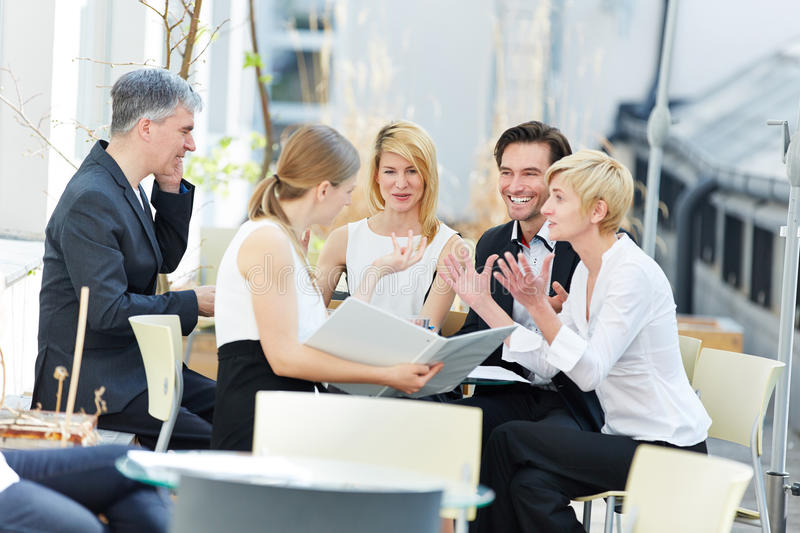 People talking about business outdoors in coffee shop royalty free stock image