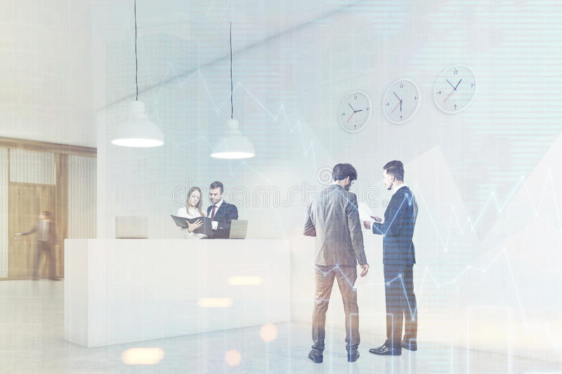 People are talking in a hall near reception counter with clocks royalty free stock images