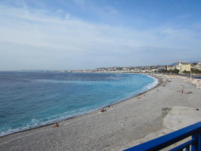 People tanning on a rocky beach in Nice, France on a beautiful O royalty free stock photos