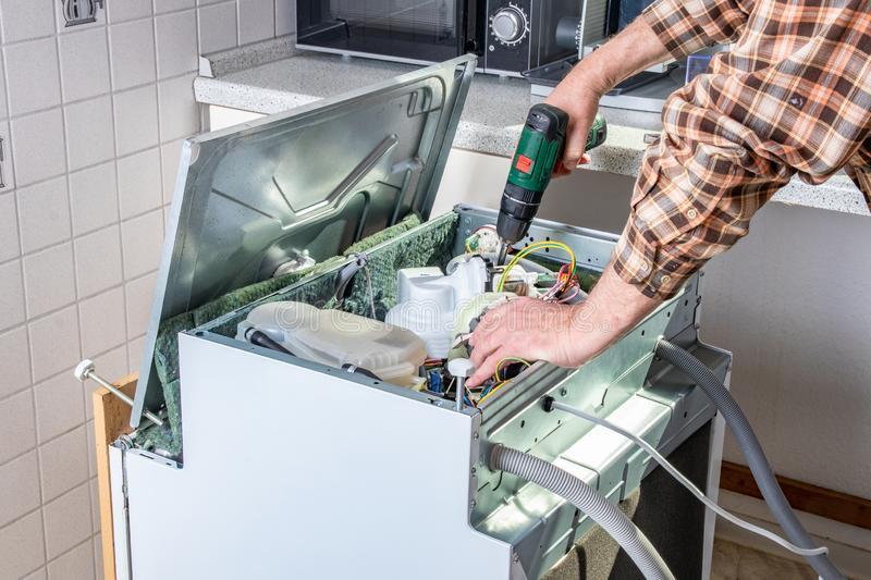 People in technician jobs. Appliance repair technician or handyman works on broken dishwasher in a kittchen. Laborer is changing royalty free stock image