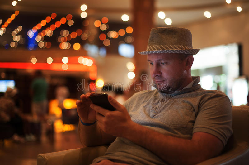 People and technology concept - happy man with smartphone reading message at bar or pub stock image