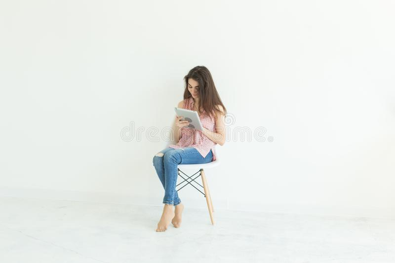People, technology and education concept - young student woman sitting on a chair and using a tablet on white background stock photography