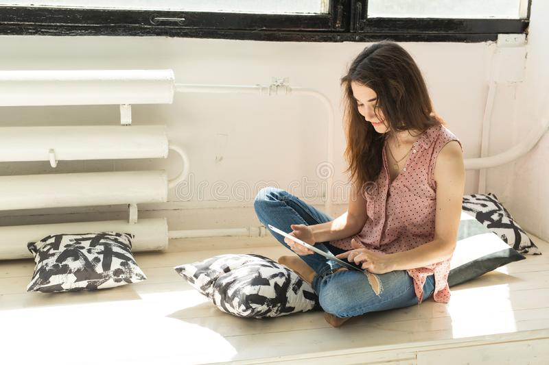People, technology and interior concept - happy young woman sitting on the floor with tablet computer with pillows stock photos
