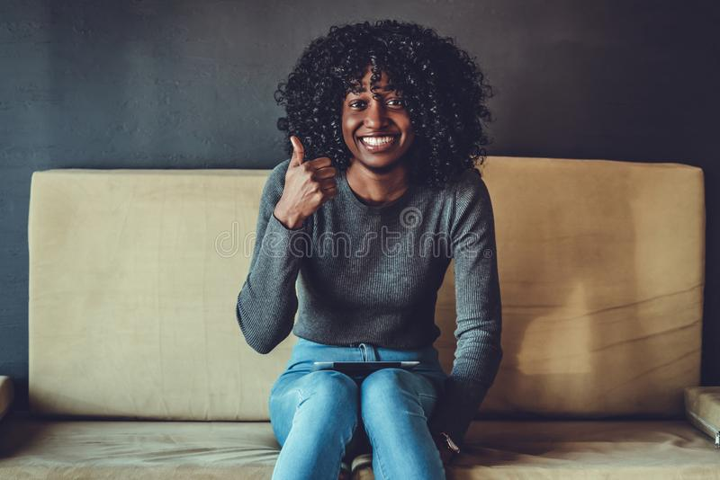 happy african american young woman sitting on sofa with laptop and showing thumbs up stock photography