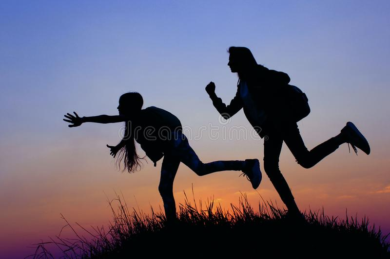 Silhouette Of A Young Girls On A Mountain Top.Young Girls With Backpack Enjoying Sunset. Female Friends Playing Outdoors. stock photos