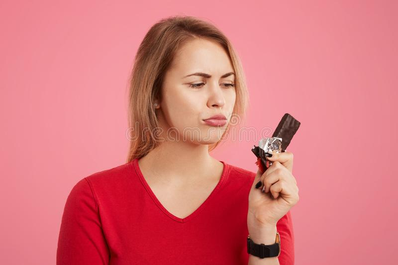 People, temptation and dieting concept. Photo of female holds sweet bar of chocolate, keeps to diet, wants to eat something sweet, stock photos