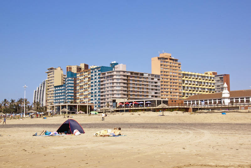 People and Tent on Beach in Durban. Many unknown people and tent on beach in front of residential and commercial buildings on Golden Mile Beachfront in Durban royalty free stock photo