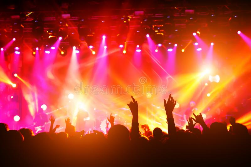 People with their hands up at a concert of their favorite group stock image