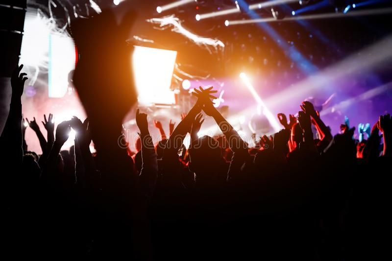 People with their hands up at a concert of their favorite group royalty free stock images
