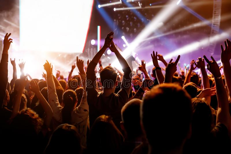 People with their hands up at a concert of their favorite group royalty free stock photography
