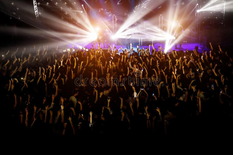 People with their hands up at a concert of their favorite group stock images