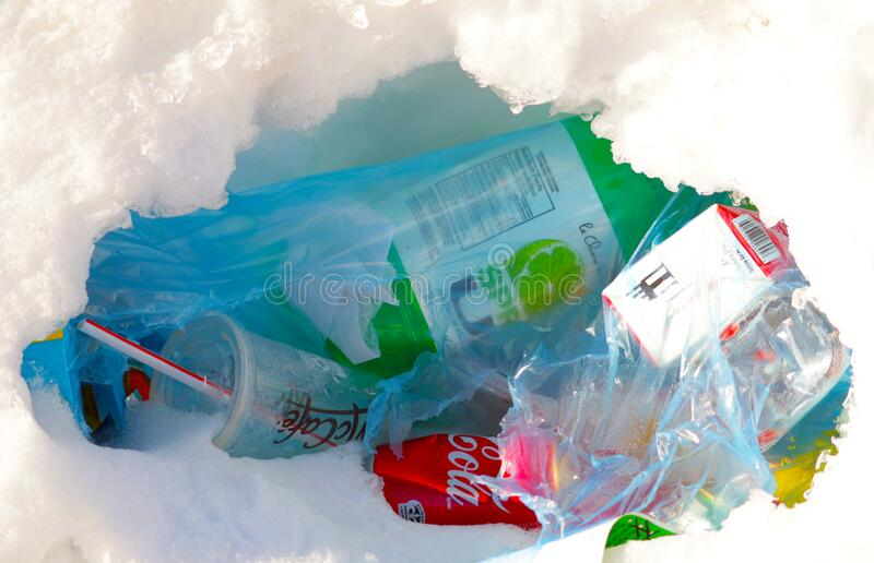 People throw coffee cups on snow. A pile of abandoned garbage on the street. Scattered food waste, cans of cola, beverage, fast. People throw coffee cups on stock photos