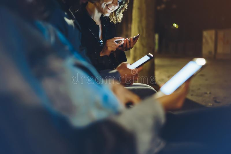 People together pointing finger on screen smartphone on background bokeh light in night atmospheric city, group adult hipsters fri. Ends using in hands modern royalty free stock photos