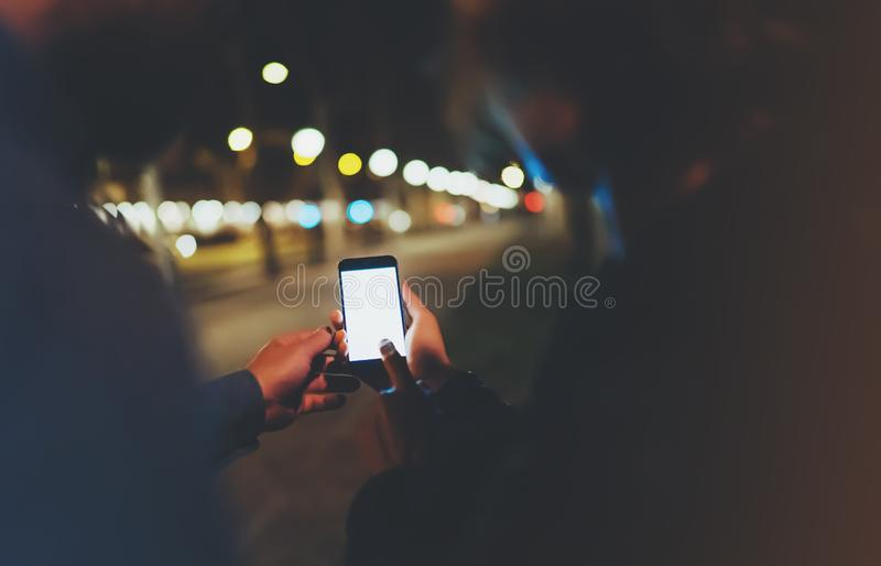 People together pointing finger on screen smartphone on background bokeh light in night atmospheric city, group adult hipsters. Friends using in hands modern stock image