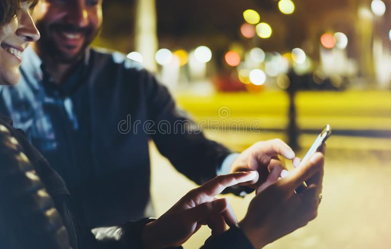 People together pointing finger on screen smartphone on background bokeh light in night atmospheric city, group adult hipsters stock images