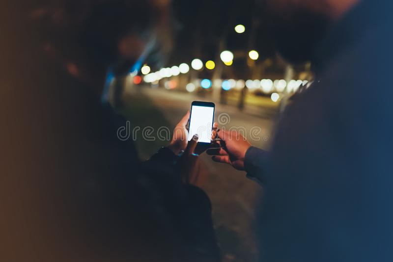 People together pointing finger on screen smartphone on background bokeh light in night atmospheric city, group adult hipsters. Friends using in hands modern royalty free stock photography