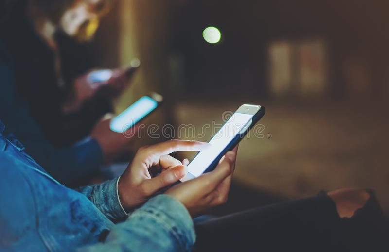 People together pointing finger on screen smartphone on background bokeh light in night atmospheric city, group adult hipsters. Friends using in hands modern stock images