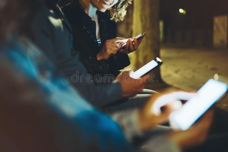 People together pointing finger on screen smartphone on background bokeh light in night atmospheric city, group adult hipsters royalty free stock image