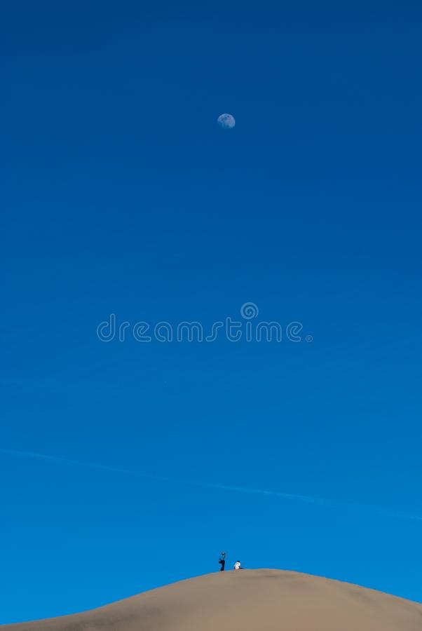 People on the top of sand dunes and the Moon stock photo