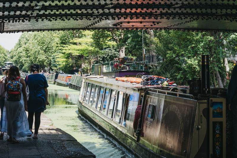 People and tour boat passing under the bridge on Regents Canal in Little Venice, London, UK. London, UK - July 18, 2019: People and tour boat passing under the stock photography