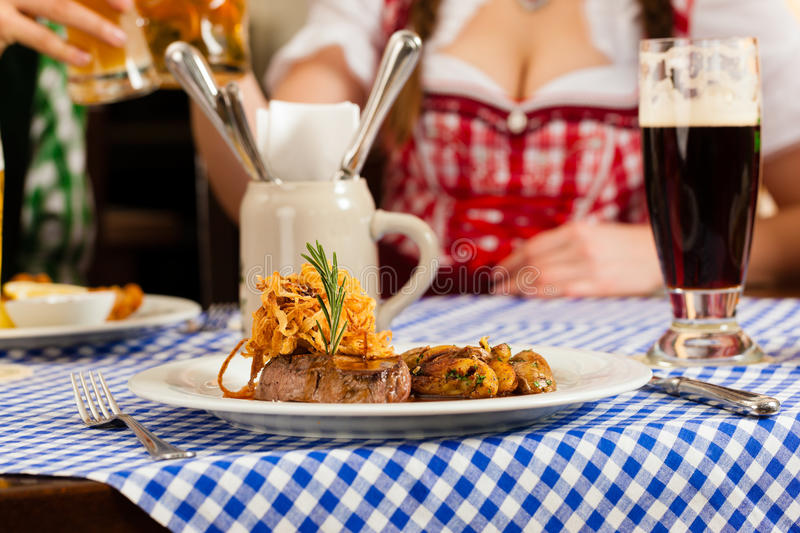 People in traditional Bavarian Tracht eating in restaurant or pub. Young people in traditional Bavarian Tracht eating in restaurant or pub lunch or dinner stock image