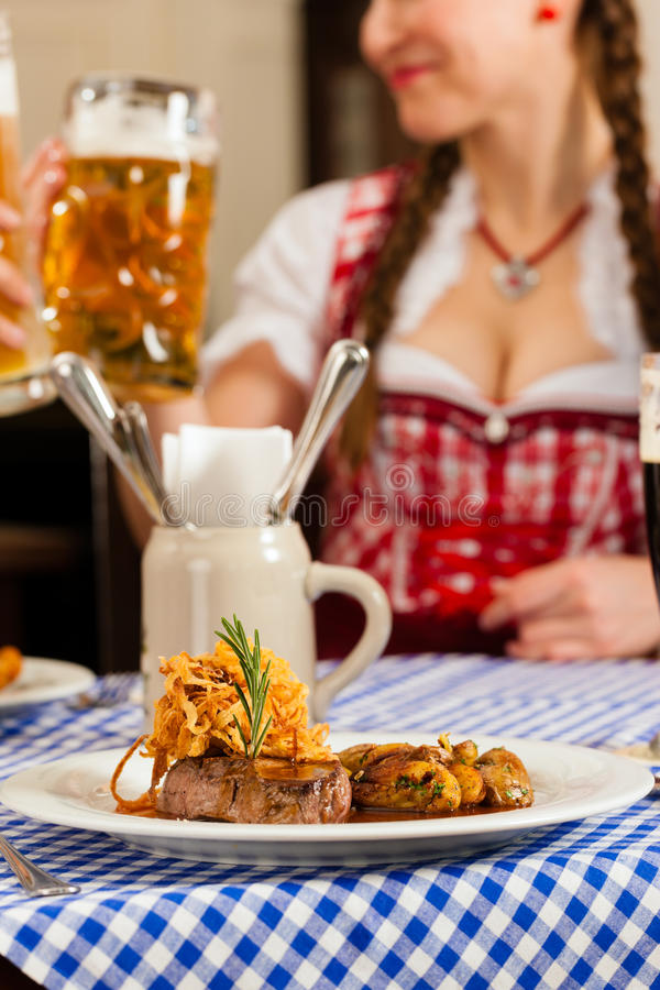 People in traditional Bavarian Tracht eating in restaurant or pub. Young people in traditional Bavarian Tracht eating in restaurant or pub lunch or dinner royalty free stock images