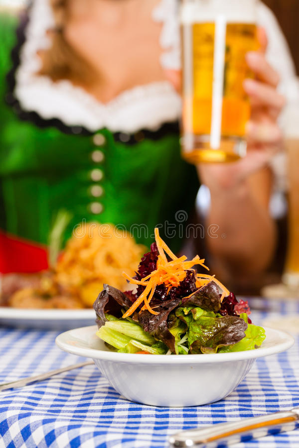 People in traditional Bavarian Tracht eating in restaurant or pub. Young people in traditional Bavarian Tracht eating in restaurant or pub lunch or dinner, focus stock photo