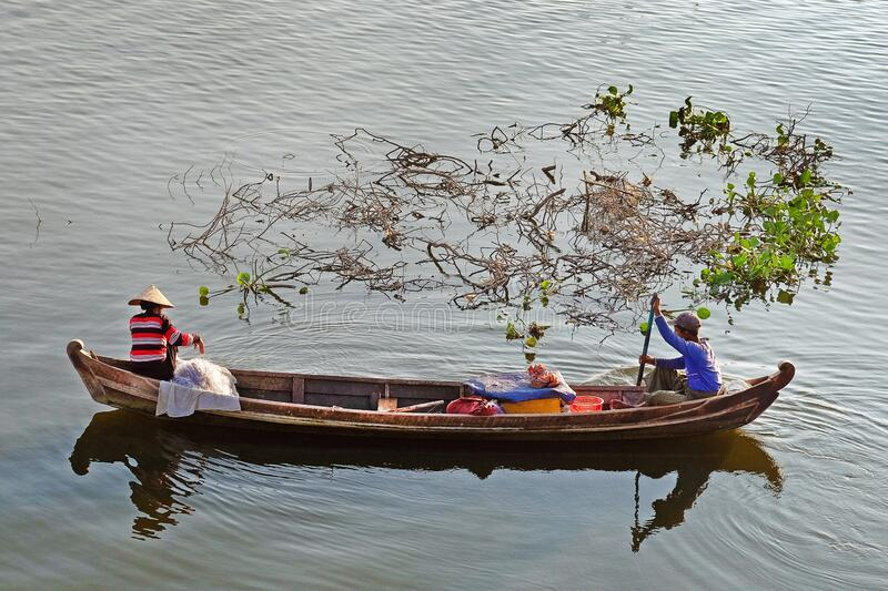 People in a traditional fishing boats on the Taung Tha Man Lake, near the U Bein Bridge, Mandalay. stock photo