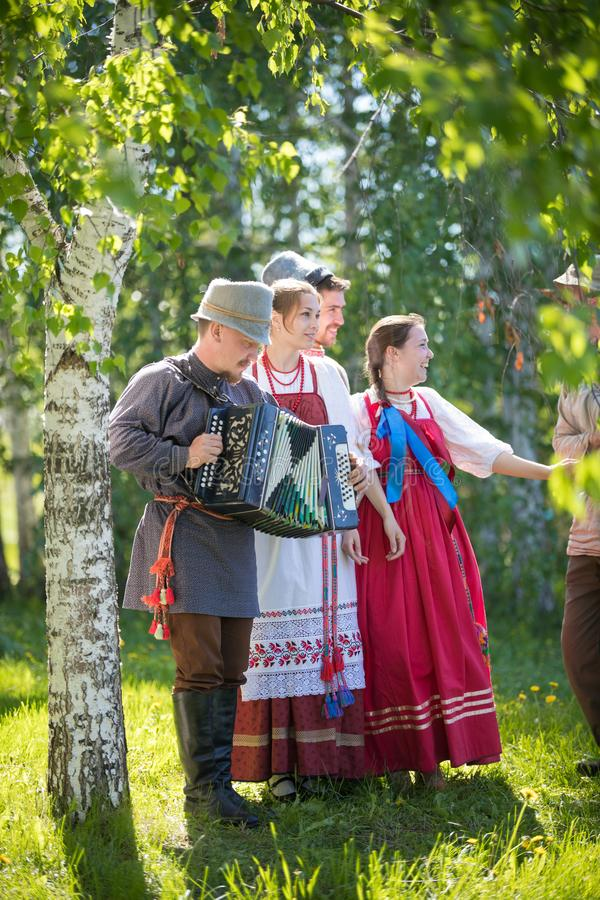 People in traditional Russian clothes are stand under a birch tree and smiling - one of them plays the accordion. Vertical view royalty free stock photo